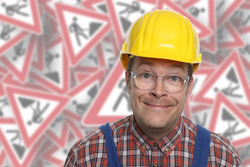 Bauarbeiter vor Baustellenschildern